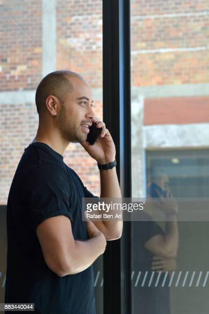 maori man talking on his mobile phone - rafael ben ari stock pictures, royalty-free photos & images