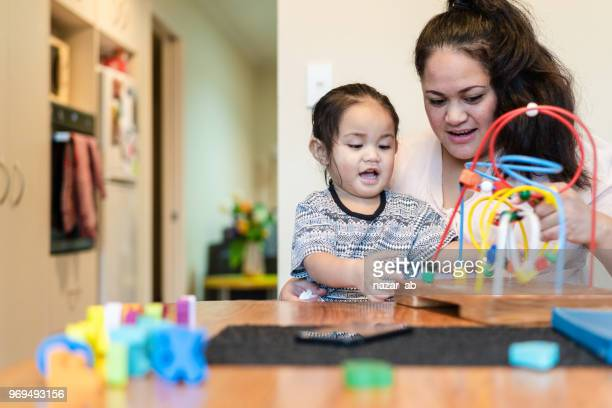 Maori mother playing with kid at home.