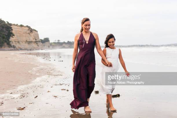 Maori mother with her daughter walking on beach.