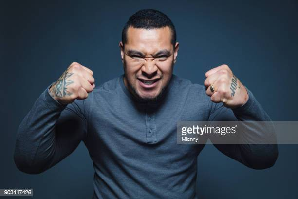maori pacific islander having fun flexing his muscles - flexing muscles stock pictures, royalty-free photos & images