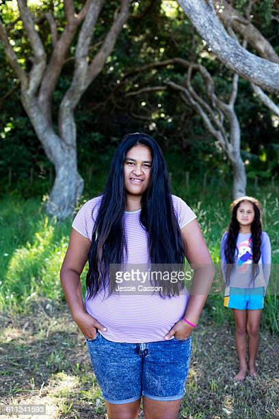 Maori teenager and younger girl in garden