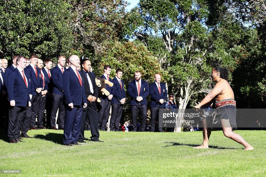 A Maori warrior (R) lays a challenge down for team manager John Spencer (6th L-front) of the British and Irish Lions during a Maori welcome ceremony at the Waitangi Treaty Grounds in Waitangi on June 4, 2017. / AFP PHOTO / POOL / Hannah Peters