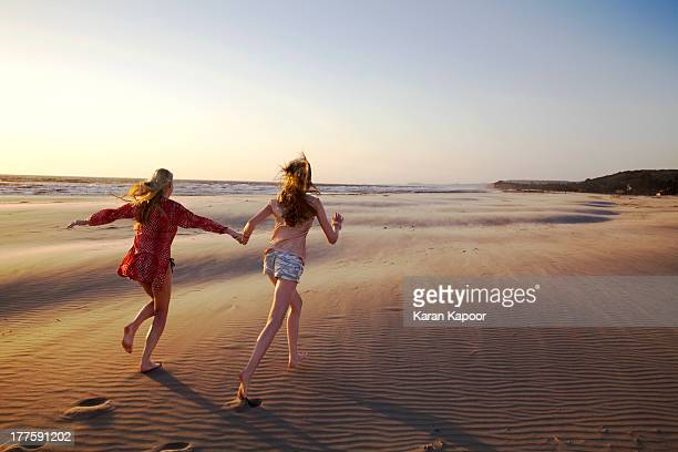 Maother and daughter running on empty beach