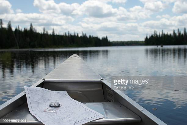 Map and compass on boat in lake, close-up