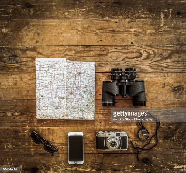 Map and travel accessories on wooden table
