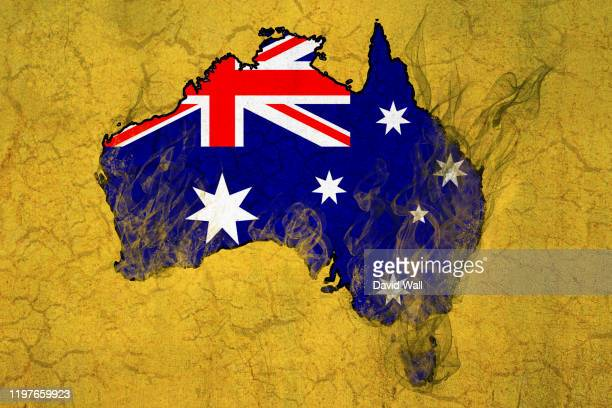 map of australia with the countries flag over layered on top. with flames and smoke burning the country. a climate change, bush fire concept. - australia stock pictures, royalty-free photos & images