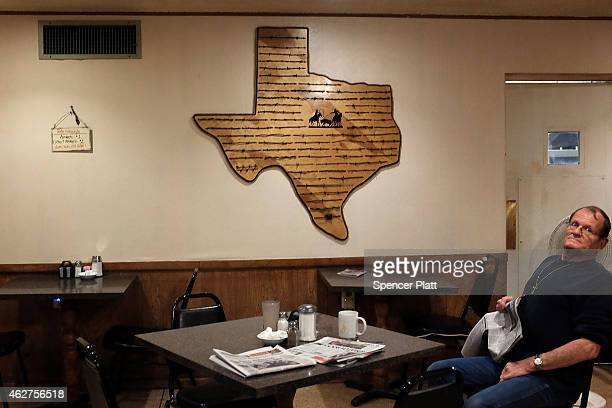 A map of Texas made of wood is viewed on a wall in a nearly empty motel restaurant that is used by many in the oil industry on February 4 2015 in...