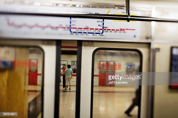 A map of the Beijing subway system sits above a closing door as people chat on the platform waiting for the next train on June 30 2006 in Beijing...