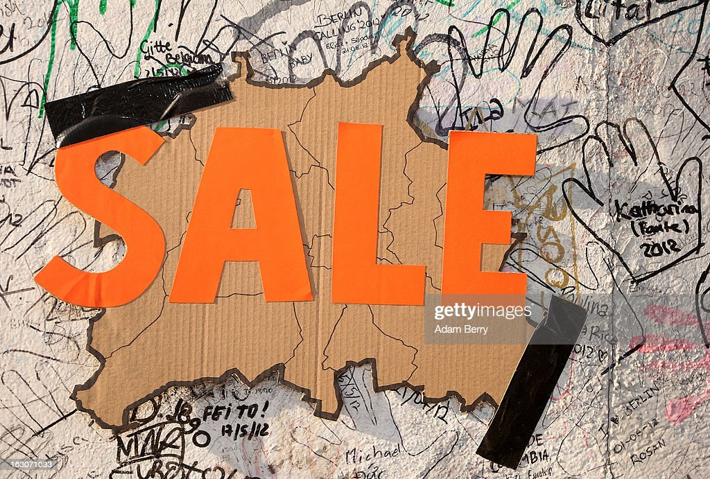 A map of the city of Berlin with the word 'SALE' written across it hangs on the East Side Gallery, the longest remaining portion of the former Berlin Wall, which has been slated for removal by a construction company to build a high-rise luxury apartment block, on March 4, 2013 in Berlin, Germany. A real estate developer is planning to build a 14-storey apartment building between the East Side Gallery and the Spree River and needs to remove the Wall section in order to allow access to the construction site. Protesters managed to temporarily halt the dismantling of the section on March 1. Critics, including East Side Gallery mural artists and Spree River embankment development opponents, decry the move, citing the importance of the East Side Gallery's status as a protected landmark and a major tourist attraction. The East Side Gallery is approximately 1.3 kilometers long.