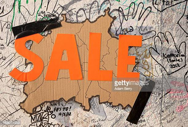 A map of the city of Berlin with the word SALE written across it hangs on the East Side Gallery the longest remaining portion of the former Berlin...