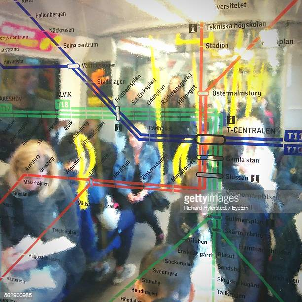 Map On Glass Window Against People Sitting In Train