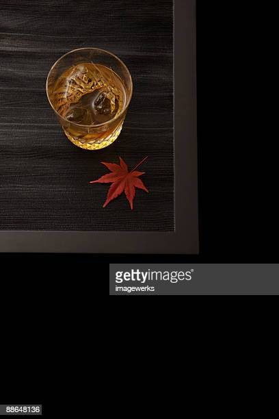Maple leaf and glass of whiskey on table