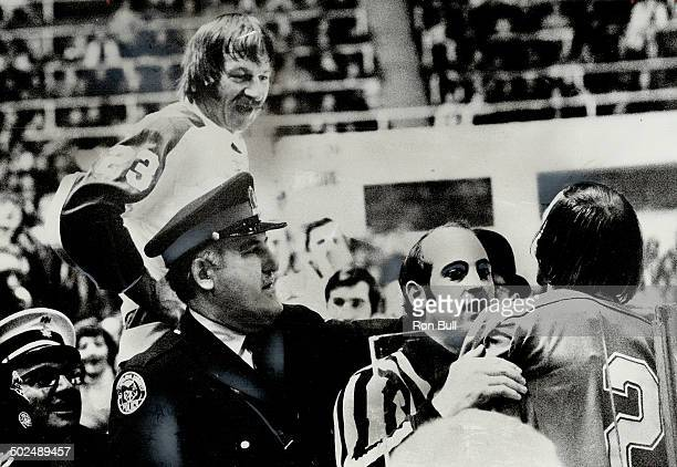 Maple leafs' Eddie Shack stands in penalty box and taunts Steve Durbano of St Louis Blues who is being restrained by linesman John D'Amico and a...
