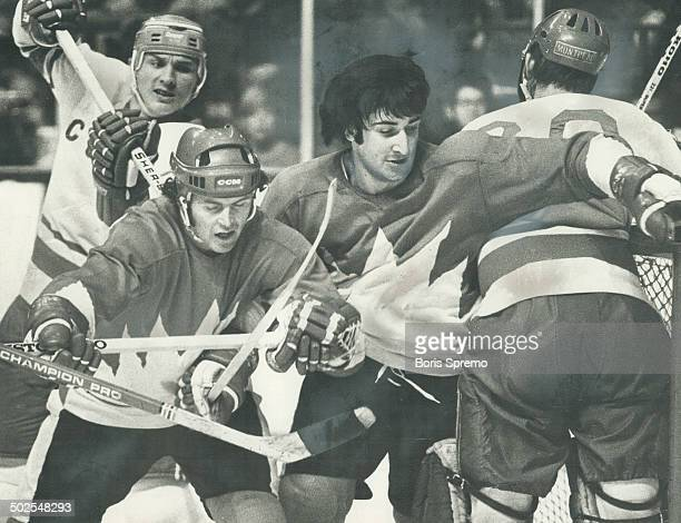 Maple leafs' Paul Henderson left foreground with helmet and Montral's Guy Lapointe must've thought they were in woods as they battled in front of...
