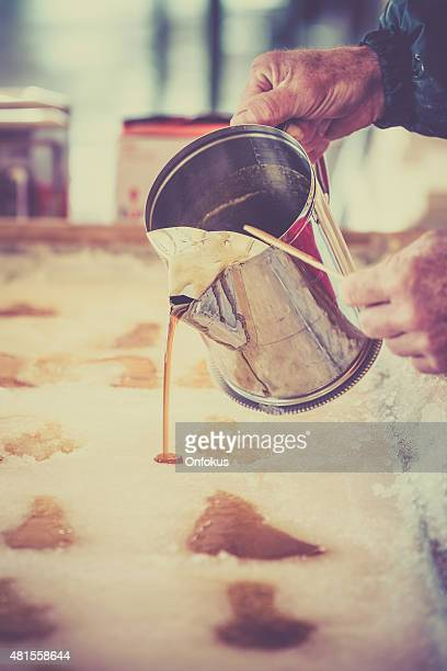 maple sugar taffy on snow at sugar shack - hut stock pictures, royalty-free photos & images