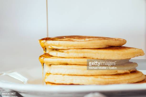 maple syrup falling on pancakes served in plate on table - pancake stock pictures, royalty-free photos & images
