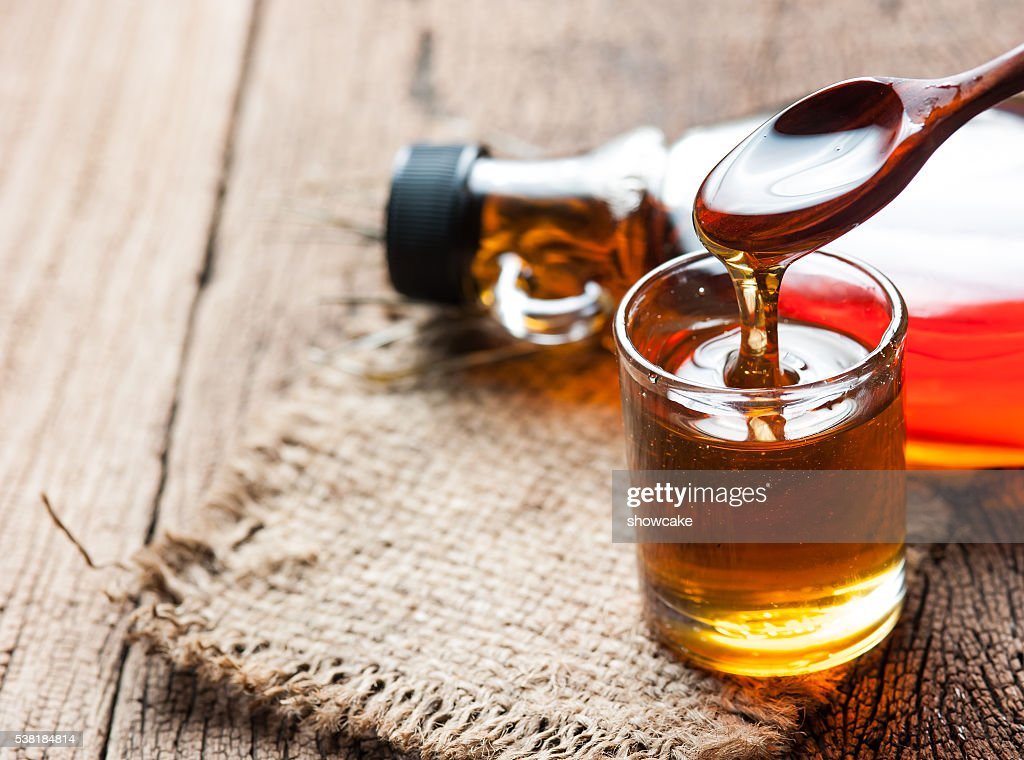 maple syrup in glass bottle on wooden table : Stock Photo