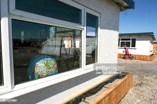 Mappemonde à une fenêtre et enfant dans le camp de réfugiés, 28 avril 2016, Grande-Synthe, banlieue de Dunkerque, France.