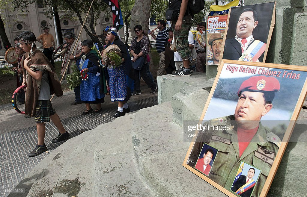 Mapuches, Chile's largest indigenous group, participate in a ceremony for the health of Venezuelan President Hugo Chavez in Santiago on January 10, 2013. With Chavez ailing and absent, Venezuela's leftist government launches a new presidential term with a display of popular support on the day he was to be inaugurated. The Supreme Court cleared the cancer-stricken president,kwho is recovering from a fourth round of cancer surgery in Havana, to indefinitely postpone his re-inauguration and said his existing administration could remain in office until he is well enough to take the oath. The government has said that he is recovering from complications from surgery, most recently a severe pulmonary infection that had resulted in a 'respiratory insufficiency.' AFP PHOTO/ Claudio Santana. AFP PHOTO /Claudio SANTANA