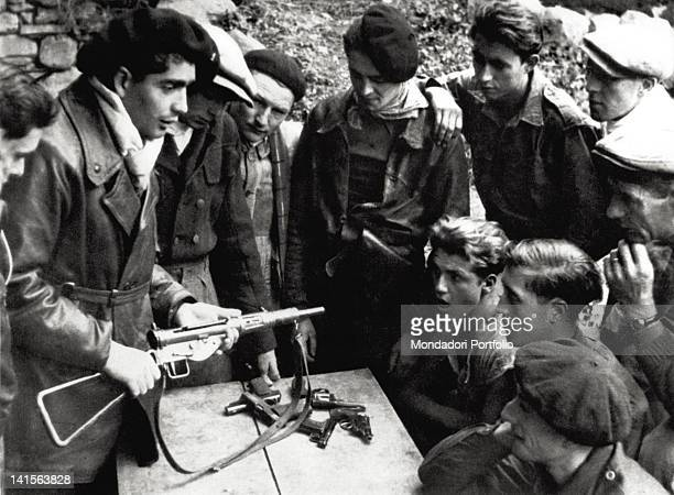 A 'maquisard' a partisan officer of the French Resistance shows a Sten submachine gun and its functions to a group of young soldiers France March 1944