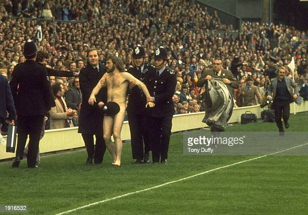 Police Constable Michael O'Brien uses his helmet to cover up streaker Bruce Perry as he is led away during the Five Nations Championship match...