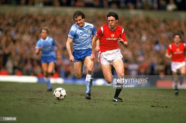 Peter Davenport of Manchester United gets away from Nicky Reid of Manchester City during a Canon League Division One match at Old Trafford in...
