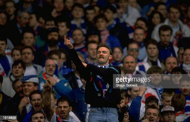 A Rangers supporter makes a rude gesture during the Scottish Premier Division match against Celtic in Glasgow Scotland Celtic won the match 20...