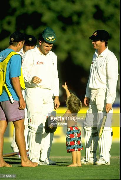 Mark Taylor and Mark Waugh of Australia enjoy the fun as a young fan invades the pitch during a match against Boland in Stellenbosch, South Africa. \...