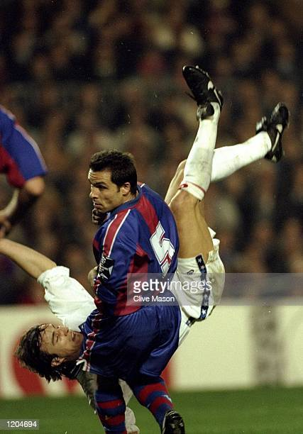David Ginola of Paris SaintGermain falls to the ground behind Sergi Barjuan of Barcelona during a match at the Nou Camp Stadium in Barcelona Spain...