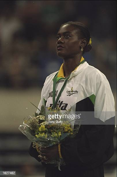 Merlene Ottey of Jamaica listens to the national anthem after receiving a medal for winning the 60 Metres event at the 1995 World Indoors in...