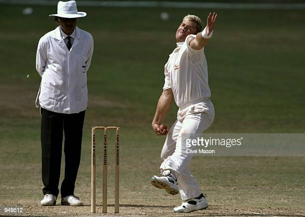 Shane Warne of Australia bowls during the First Test match against the West Indies at the Kensington Oval in Bridgetown Barbados Mandatory Credit...
