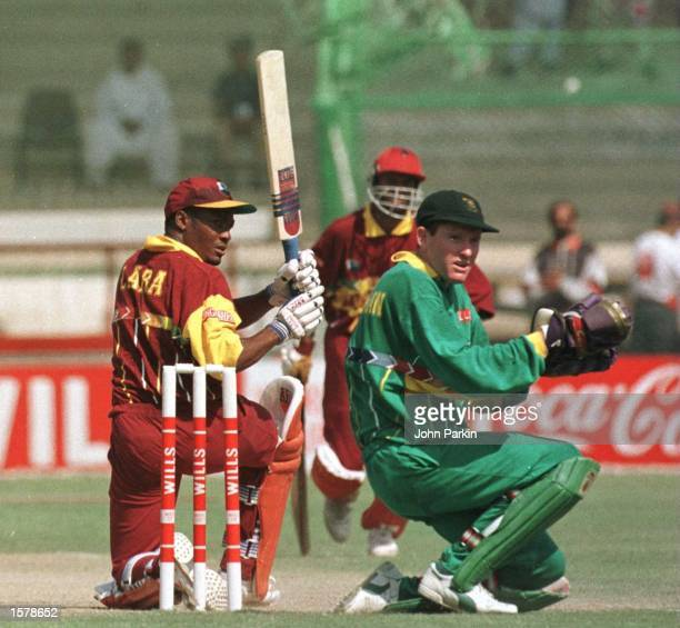Brian Lara of the West Indies sweeps a shot on his way to 111 runs as Steven Palframan of South Africa looks on during the West Indies v South Africa...