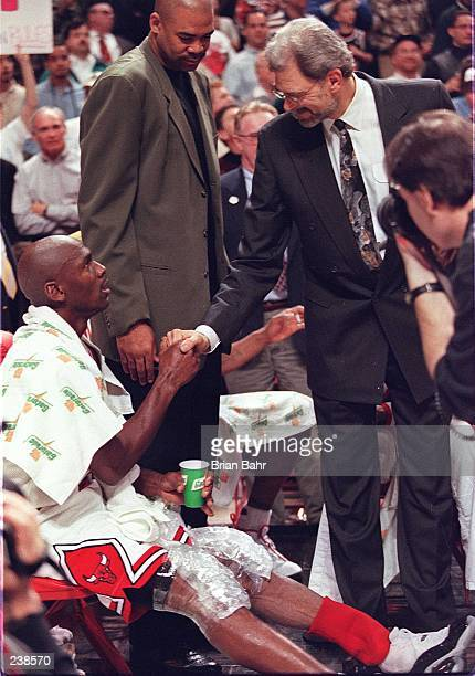 Chicago Bulls head coach Phil Jackson shakes the hand of Michael Jordan, guard for the Chicago Bulls, after Jordan left the game against the Detroit...