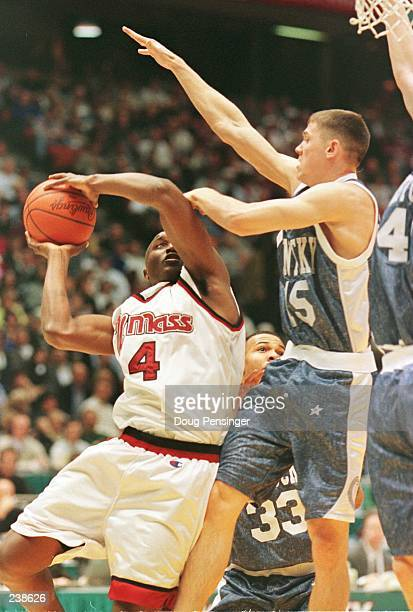 Donta Bright of the UMass Minutemen adjusts his shot in an attempt to avoid the defensive presssure applied by Jeff Sheppard of the Kentucky Wildcats...
