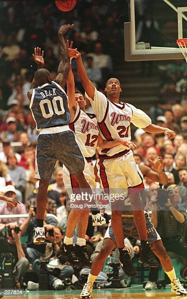 Edgar Padilla and Marcus Camby of the UMass Minutemen jumps to block the attempted shot of Tony Delk of the Kentucky Wildcats during the Minutemen''s...