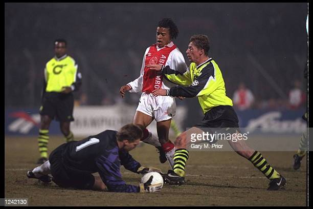 Freud and Klos of Borussia Dortmund hold off the challenge from Edgar Davids of Ajax during the Champions League match in Amsterdam