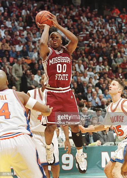 Guard Darryl Wilson of the Mississippi State Bulldogs focuses on the rim before releasing a shot over Jason Cipolla and Otis Hill of the Syracuse...
