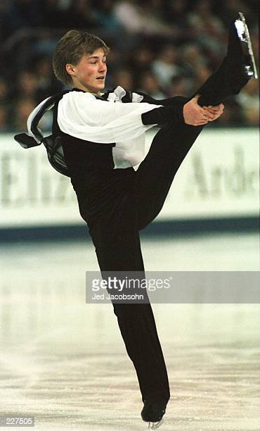 Ilia Kulik of Russia holds his leg for balance while performing a spin during his short program performance at the World Figure Skating Championships...