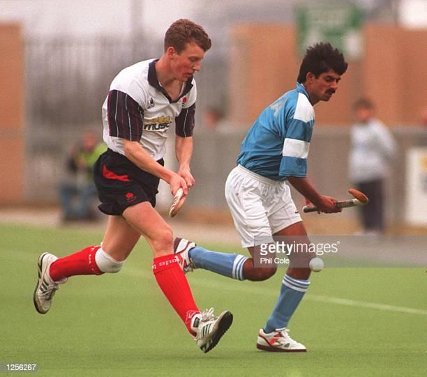 Jon Wyatt of England challenges Sanjeev Kumar Dang of India in the men's Hockey international between England and India at The Stadium Milton Keynes...