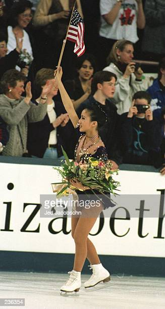 Michelle Kwan of the USA skates a victory lap while waving an American flag, following her free skate performance that earned her the gold medal at...