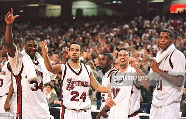 Tyrone Weeks, Carmelo Travieso, Edgar Padilla and Marcus Camby of the UMass Minutemen poses for a portrait while celebrating in the final seconds of...