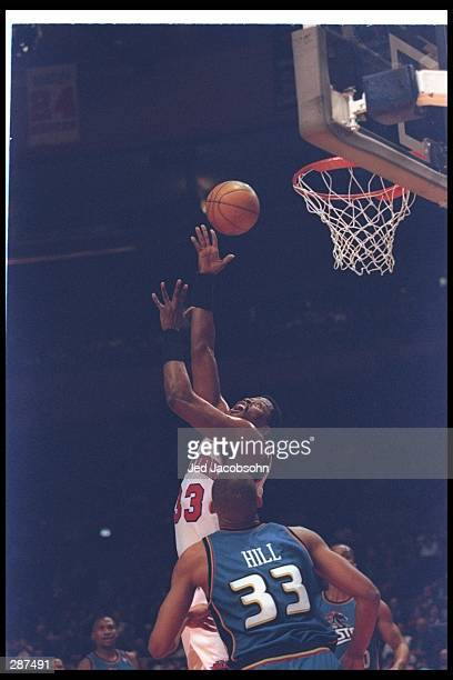 Center Patrick Ewing of the New York Knicks goes up for the ball as Detroit Pistons forward Grant Hill looks on during a game at Madison Square...