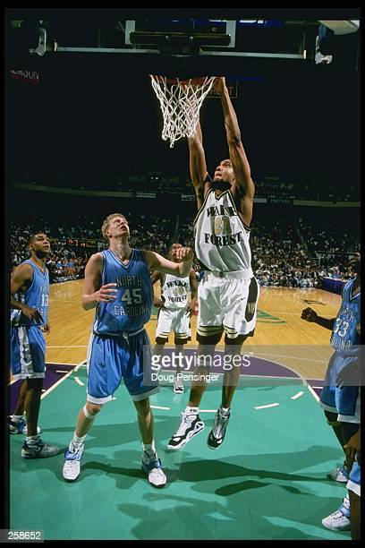Center Tim Duncan of the Wake Forest Demon Deacons slam dunks the ball as center Serge Zwikker of the North Carolina Tarheels watches him during a...