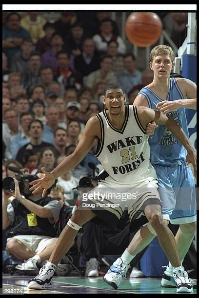 Center Tim Duncan of the Wake Forest Demon Deacons tries to break free of center Serge Zwikker of the North Carolina Tarheels during a playoff game...