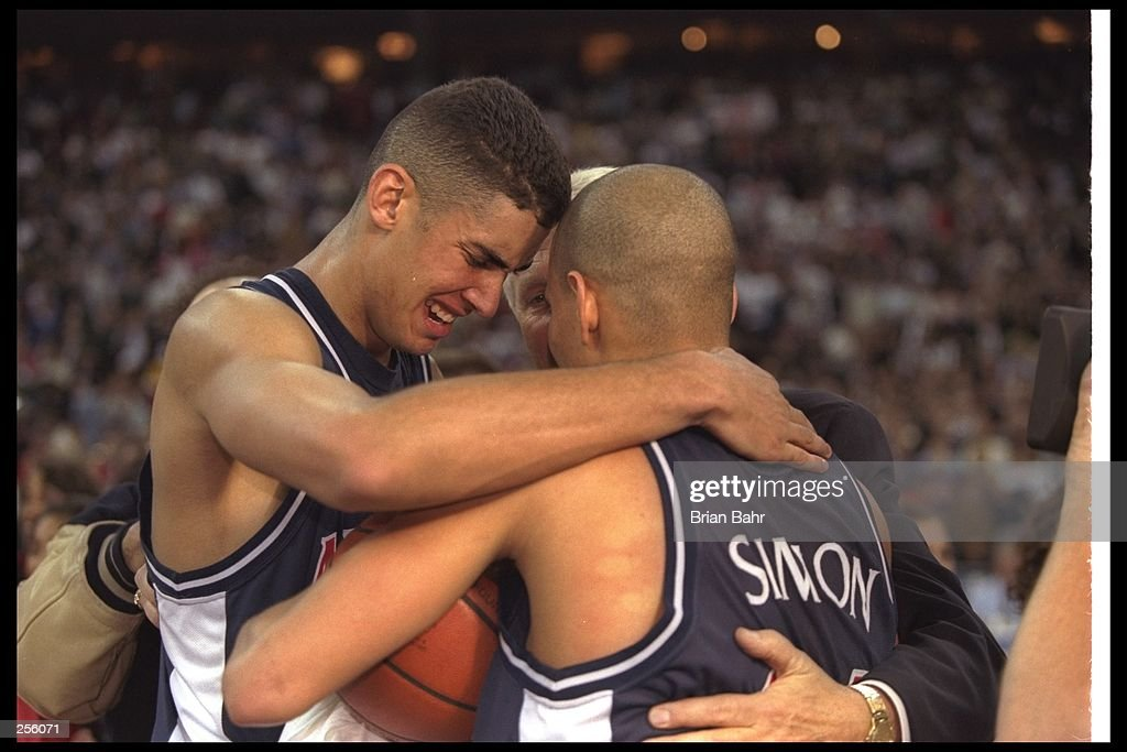 Coach Lute Olson of Arizona Wildcats hugs guard Miles Simon and center AJ Bramlett after the NCAA Championship game against the Kentucky Wildcats at the RCA Dome in Indianapolis, Indiana. Arizona won the game 84 - 79. Mandatory Credit: Bria