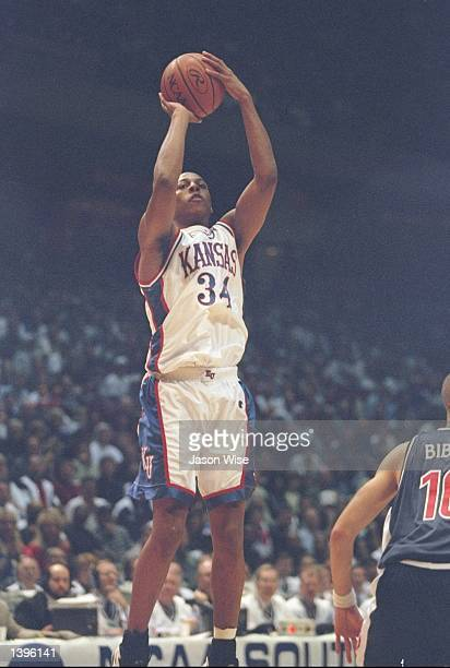 Forward Paul Pierce of the Kansas Jayhawks goes up for a score as guard Mike Bibby of the Arizona Wildcats looks on during a playoff game at the...