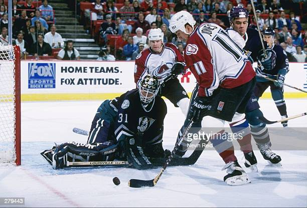 Goaltender Guy Hebert of the Anaheim Mighty Ducks and Colorado Avalanche rightwinger Keith Jones fight for the puck during a game at McNichols Sports...