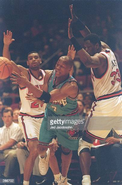 Guard Anthony Peeler of the Vancouver Grizzlies passes the ball as center Patrick Ewing and guard Allan Houston of the New York Knicks go for the...