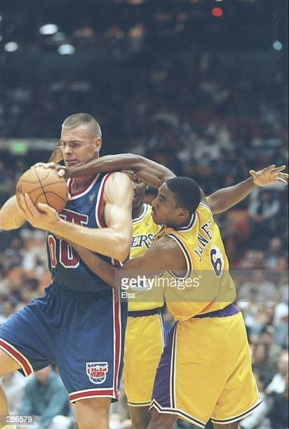 Guard Eddie Jones of the Los Angeles Lakers fights for the ball with forward Eric Montross of the New Jersey Nets during a game at the Great Western...