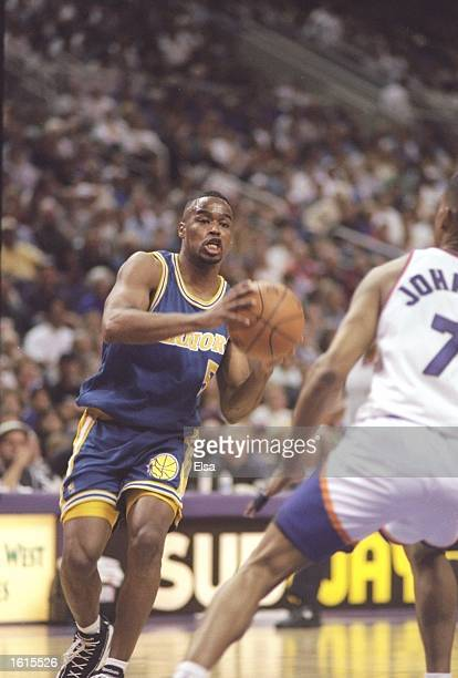 Guard Melvin Booker of the Golden State Warriors tries to fend off guard Kevin Johnson of the Phoenix Suns at the America West Arena in Phoenix...